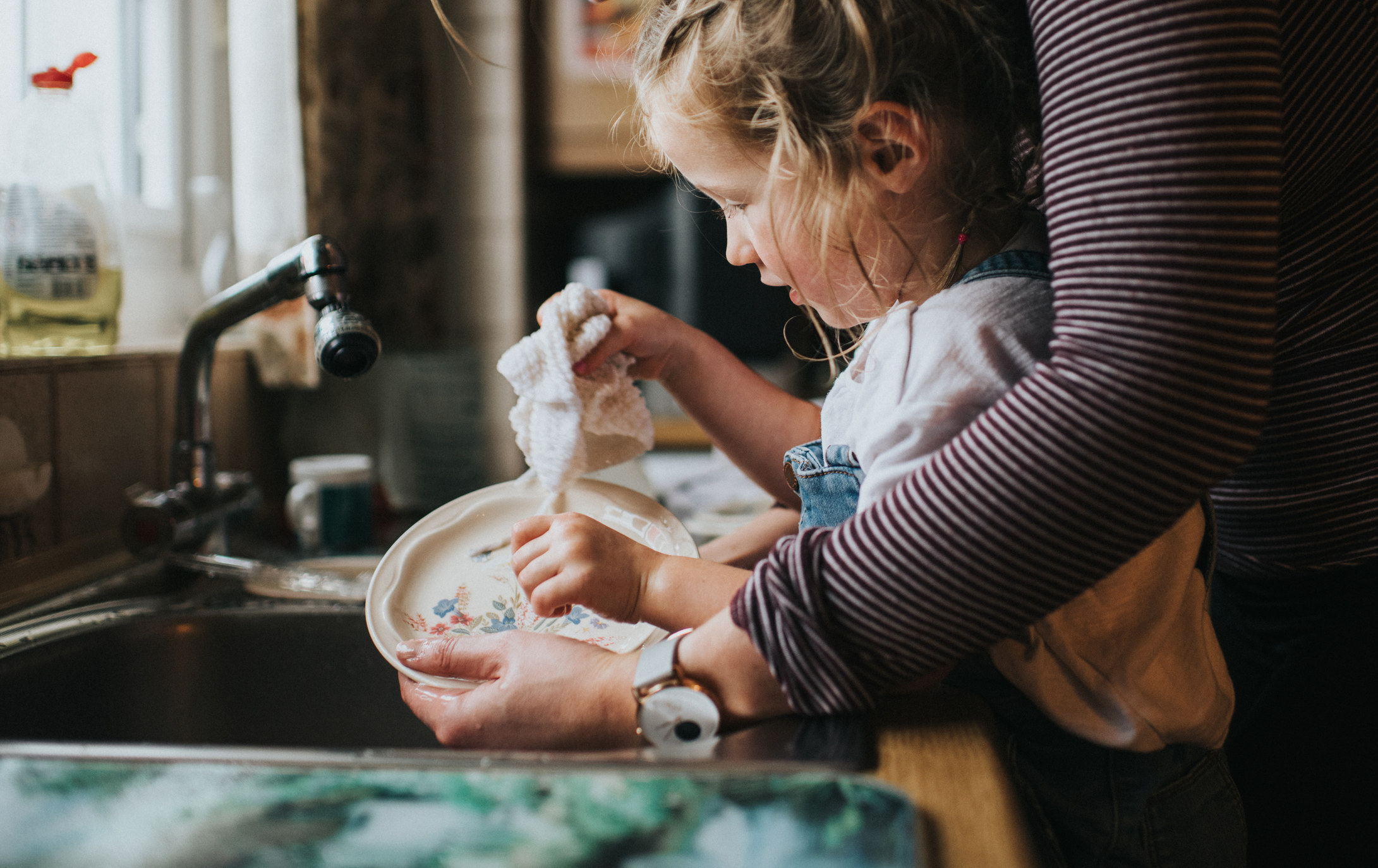 A child is helped by their parent while washing dishes