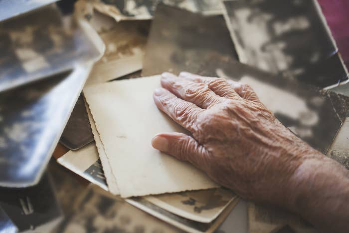 An older person's hand sits on top of a stack of papers and photographs