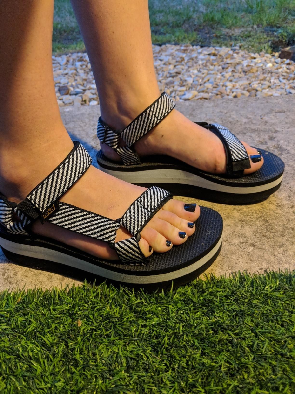 A reviewer wears the sandals in black and white stripes