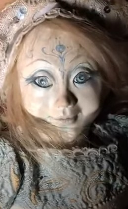 Aged doll with markings on its forehead