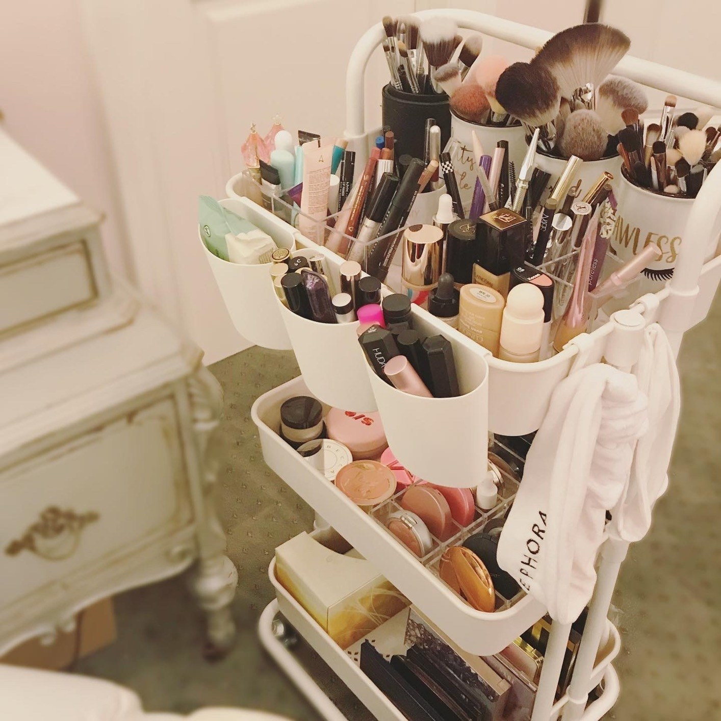 reviewer's large makeup collection stored on a rolling cart