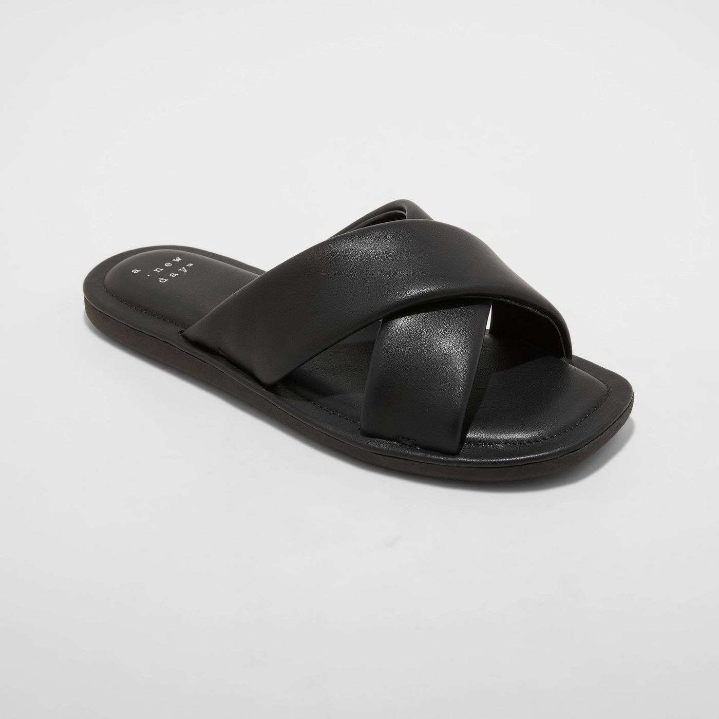 Black leather slides with black puffy sole, black stitching around the show