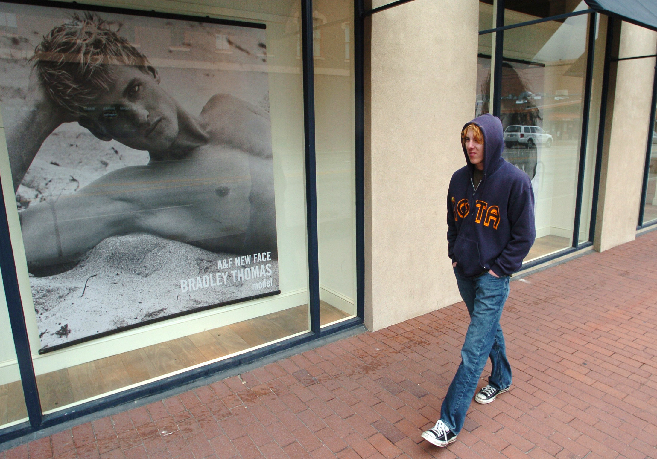 Man walking by A&F store window with a photo of a shirtless man in it