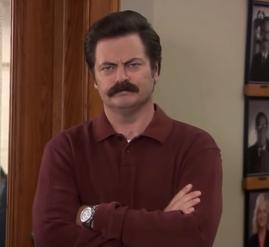 Ron Swanson from Parks and Rec with hands folded and frowning