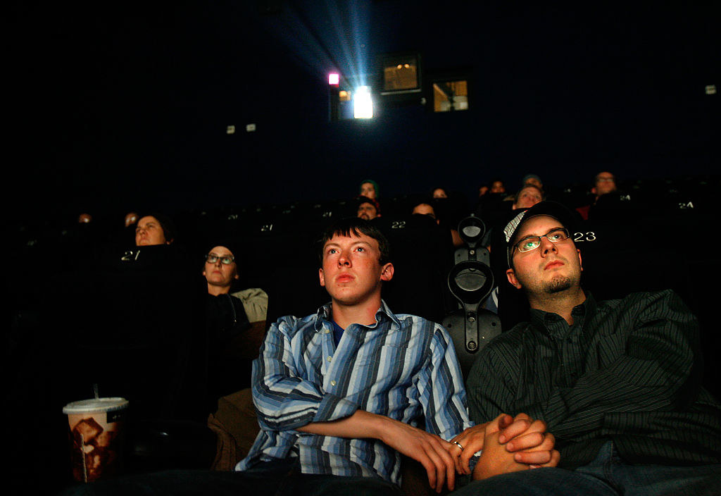 a gay couple holding hands in a movie theatre
