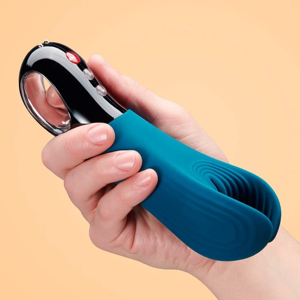 Teal silicone stroker with ribbed opening and black plastic handle