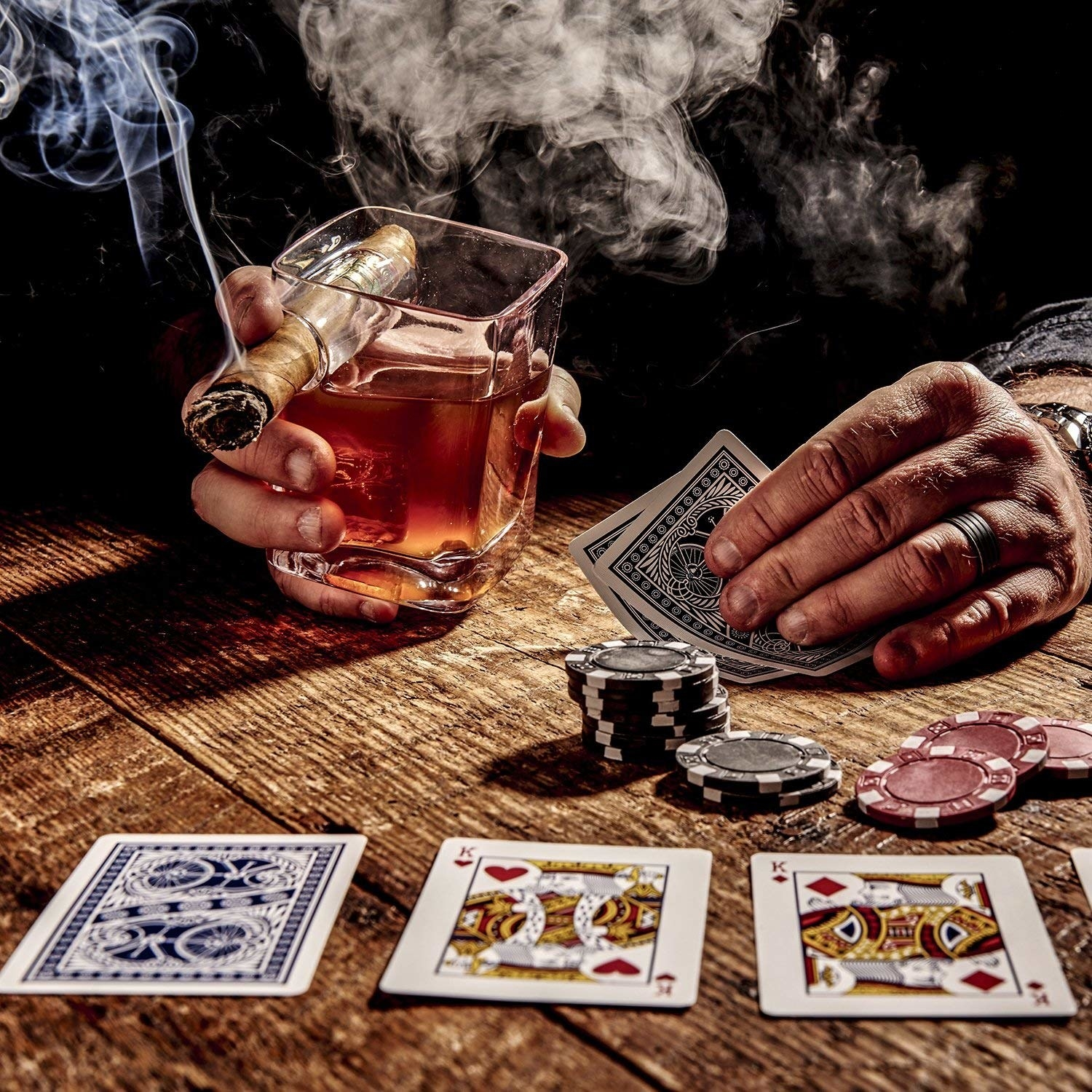 man playing cards with scotch glass and cigar in his left hand