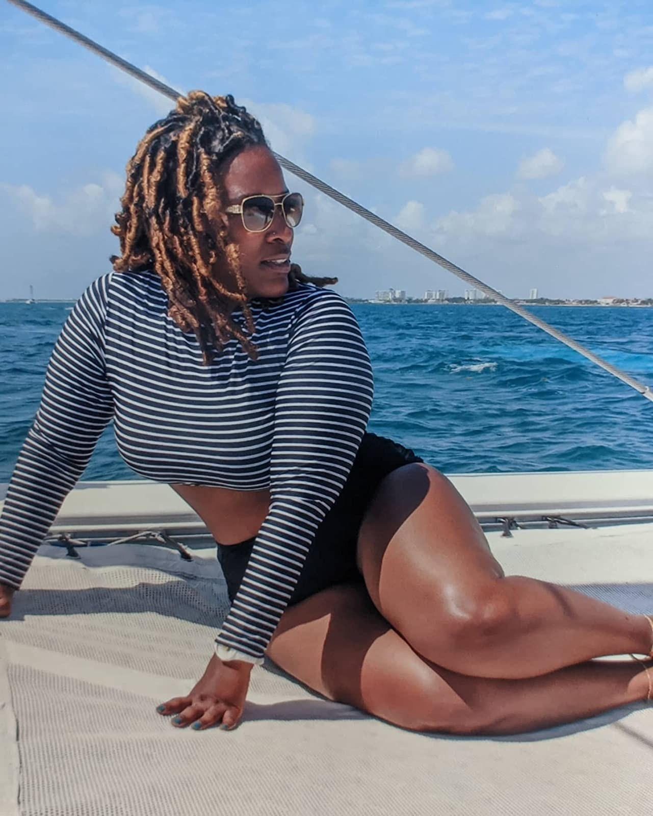 reviewer wearing the black striped rash guard tankini set on a boat