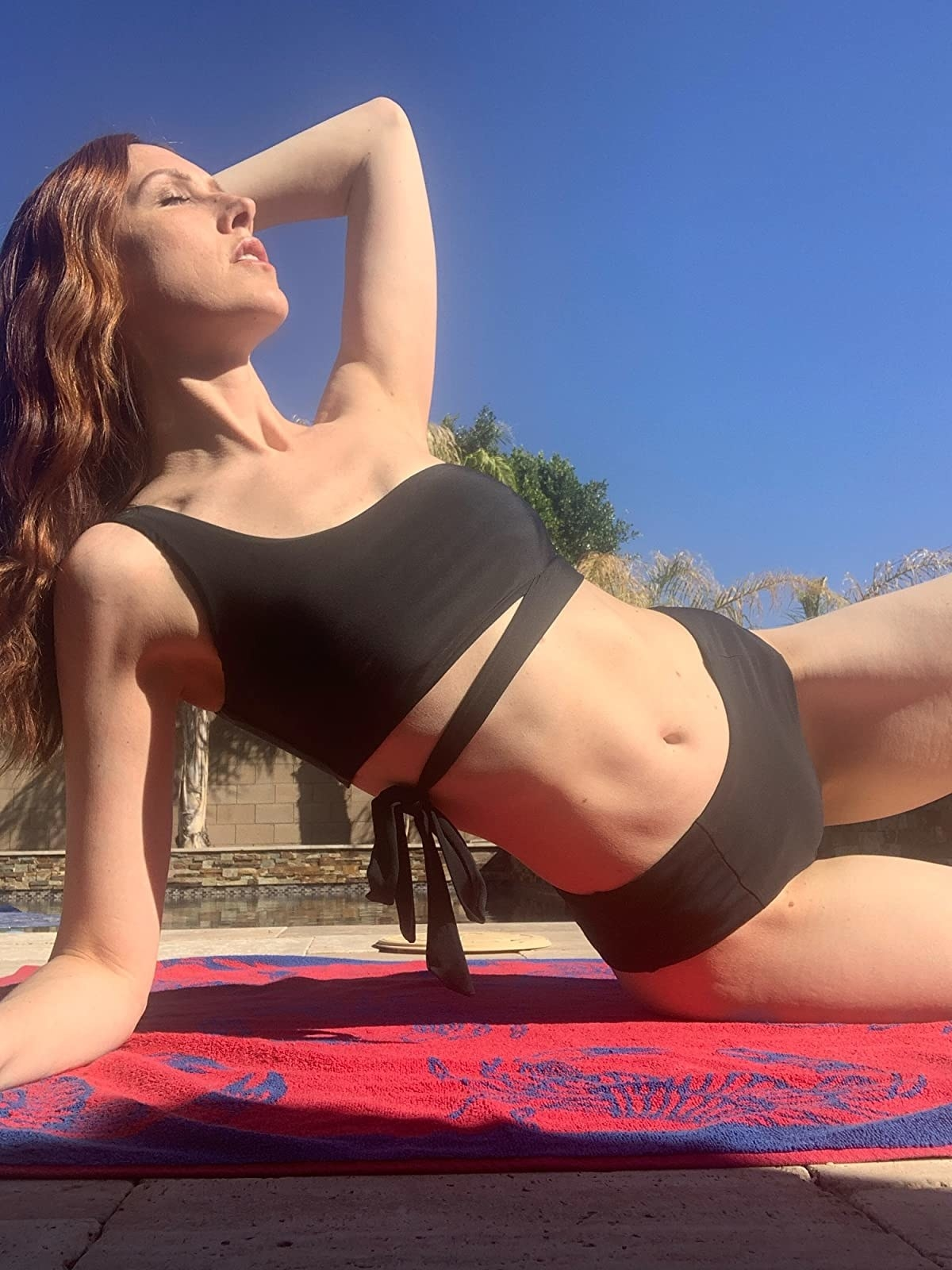 image of reviewer lounging while wearing the black one shoulder bikini set