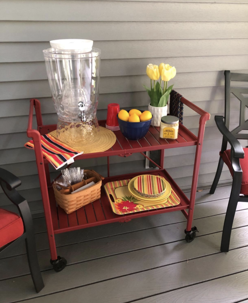 Reviewer shows outdoor cart stacked with dining supplies and a water pitcher.