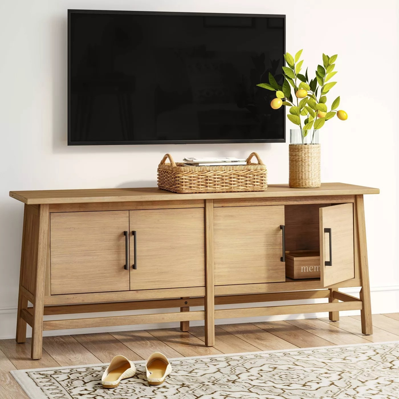 The natural TV stand with two sets of cabinets and black handles