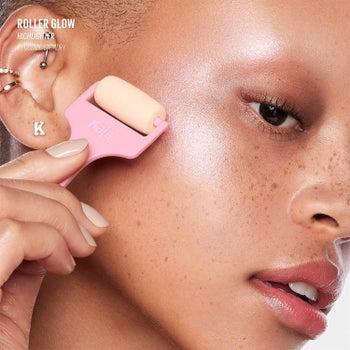 model using the highlighter roller on her cheekbone