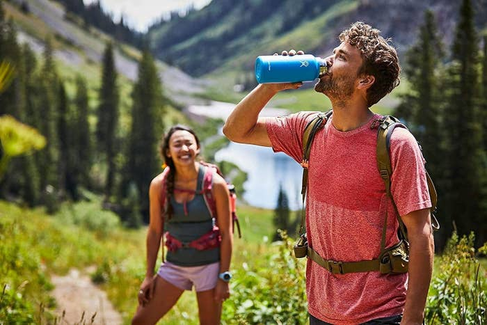 A model drinks from a blue Hydroflask