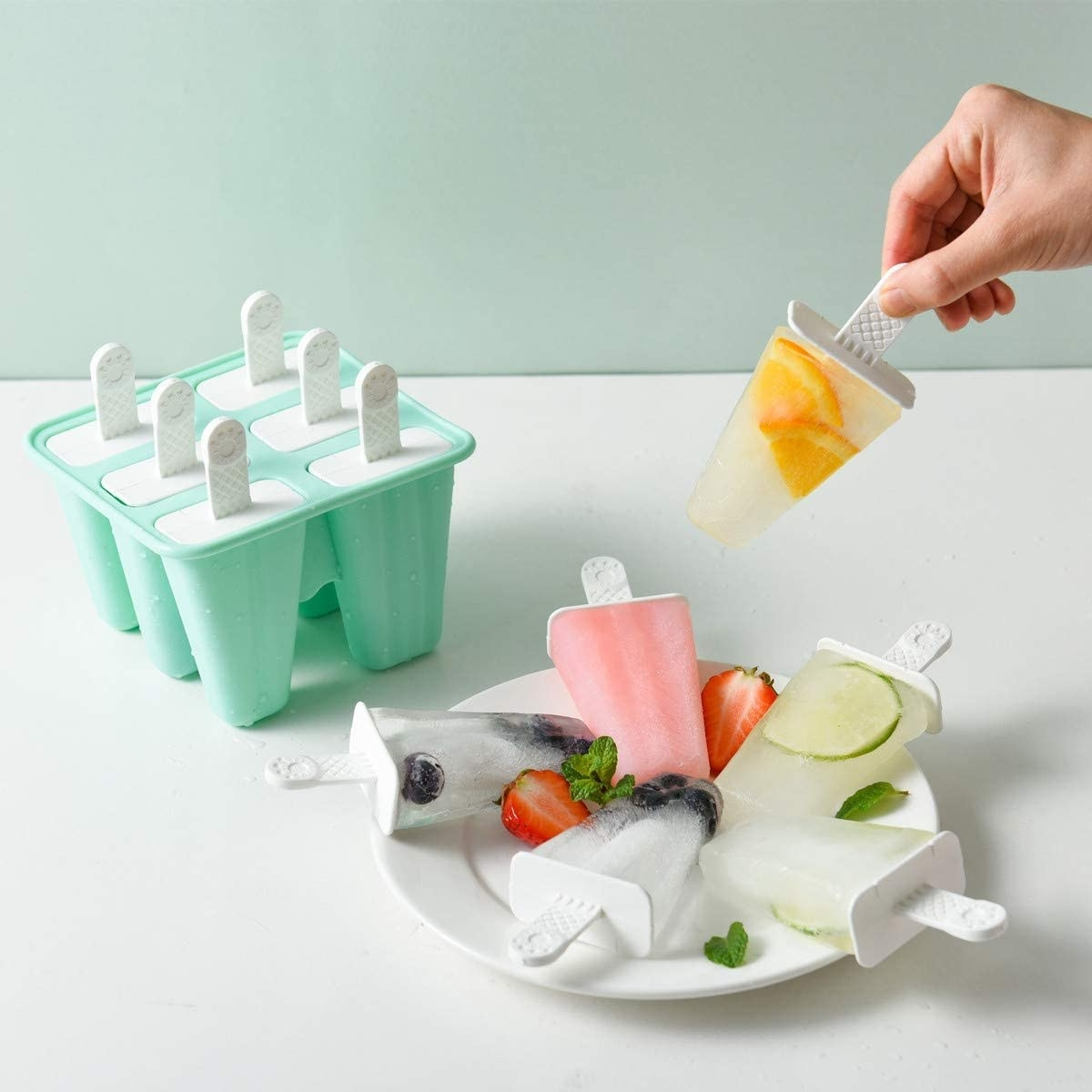 Model holding homemade popsicle next to ice pop mold