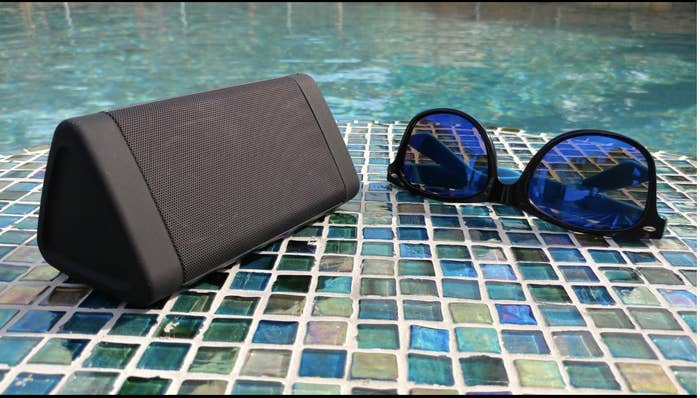 Reviewer's speaker sits on the ground next to the edge of a pool