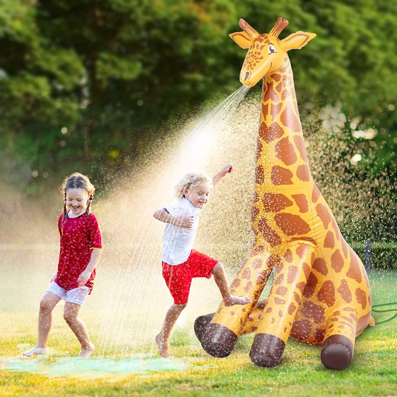 Kids playing underneath giraffe-shaped sprinkler