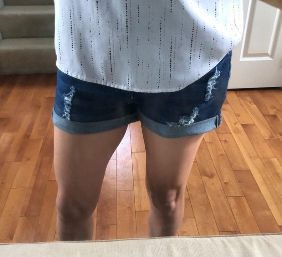 Reviewer wearing the denim shorts with distressed details