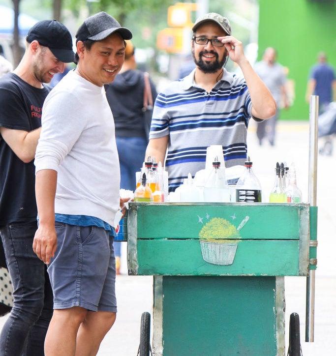 Jon talking to Lin as he walks with his piragua cart
