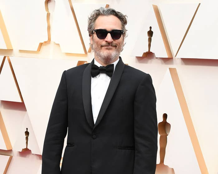 Joaquin wears sunglasses and a tux on the Oscars red carpet