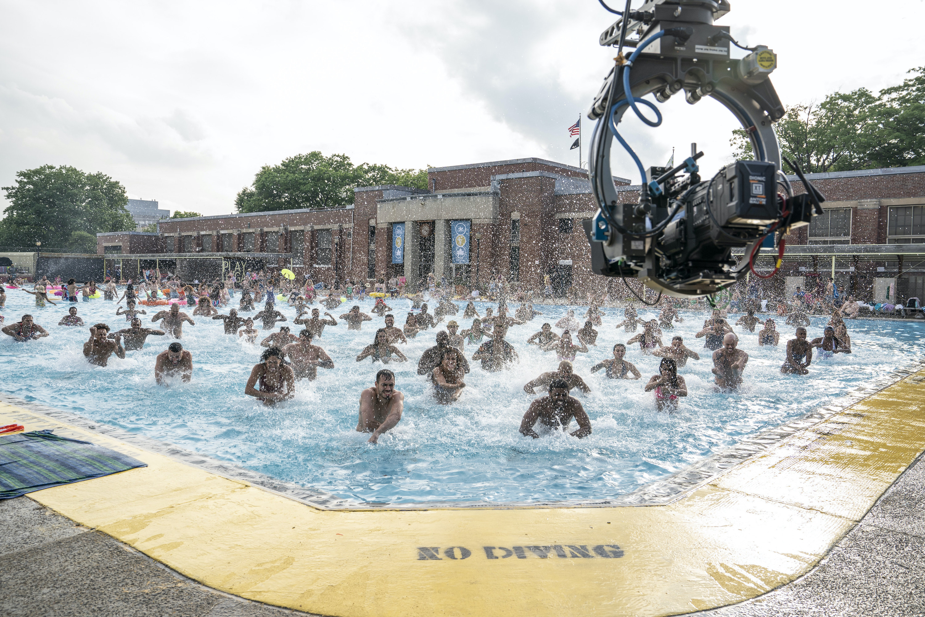 A big camera rig shooting the people dancing in the pool from above