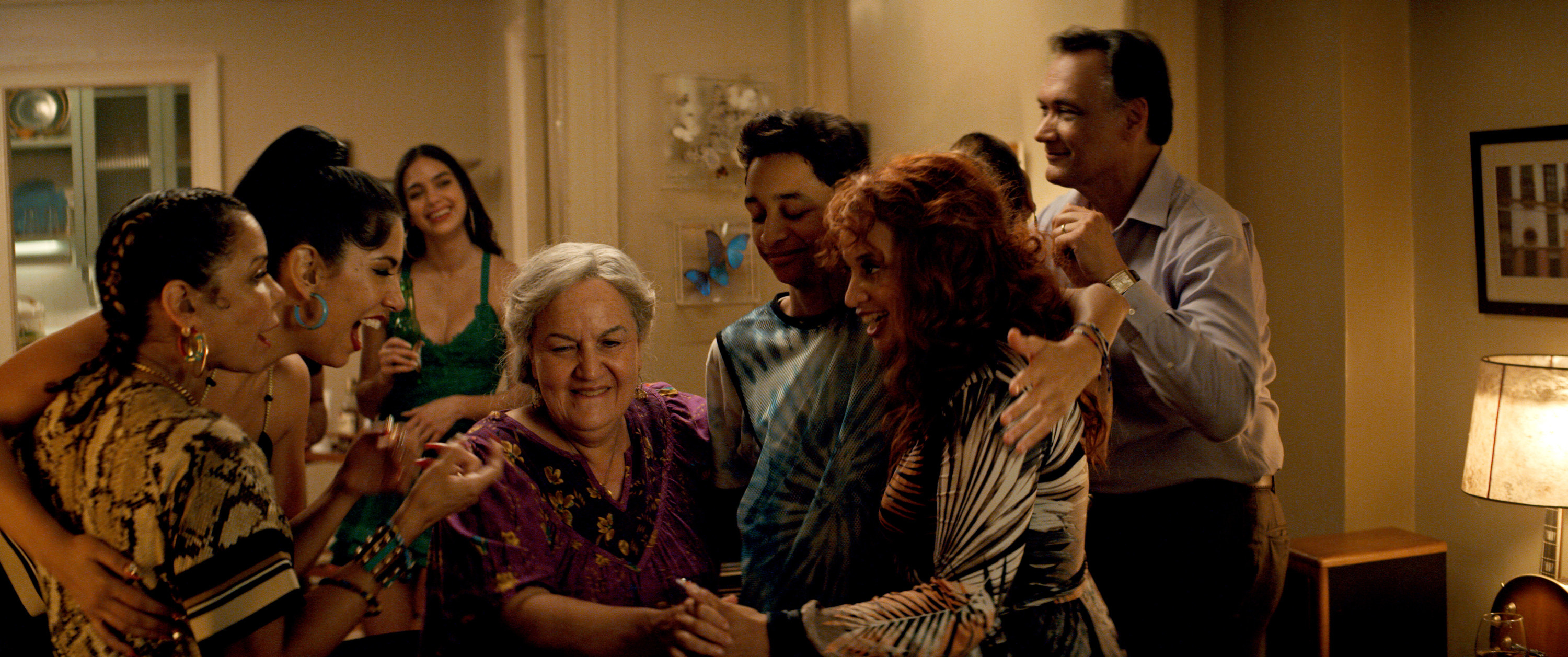 The cast of In The Heights hugging Abuela Claudia in the film