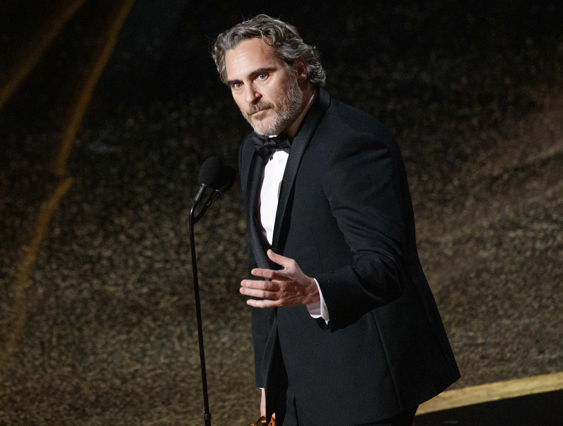 Joaquin looks serious while speaking onstage