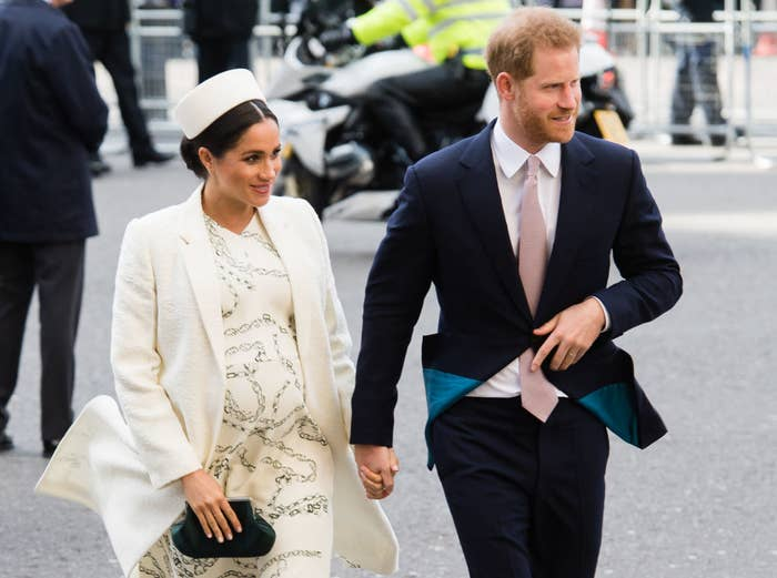 Harry holding hands with a pregnant Meghan as they cross the street