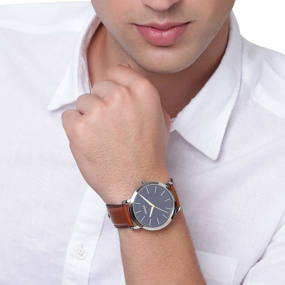 A person wearing the blue watch with the brown straps
