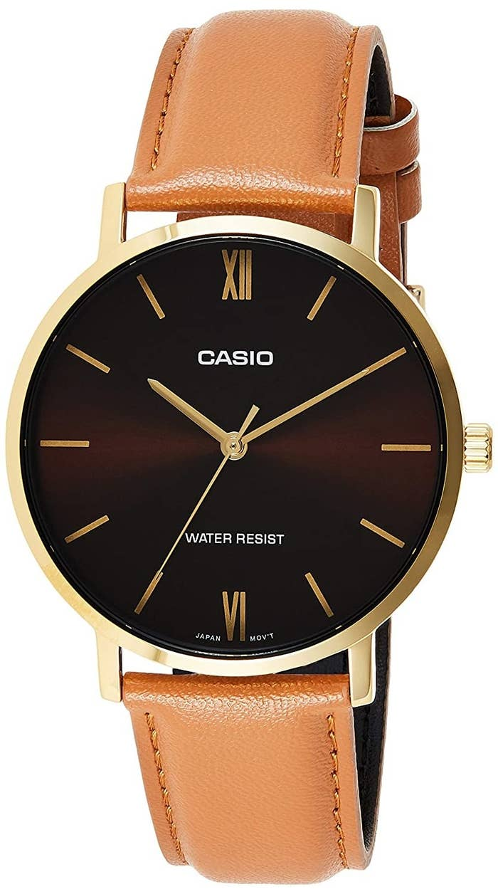 A Casio watch with a brown strap, dark brown dial, and golden hands