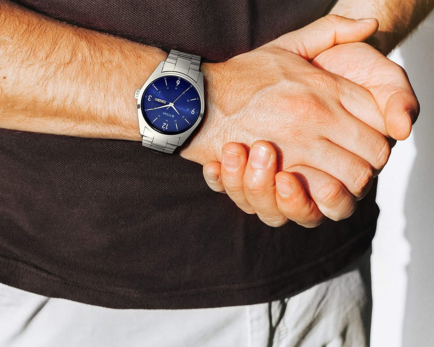 A man wearing a blue and silver watch