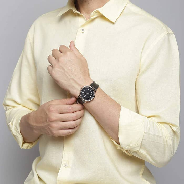 A man in a yellow shirt wearing a black and gold Timex watch