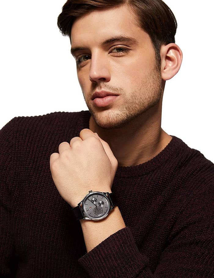 A man wearing the watch which has black leather straps and a dark grey dial