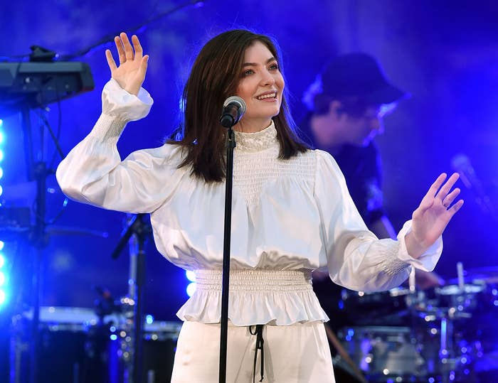 Lorde dances in a white outfit onstage