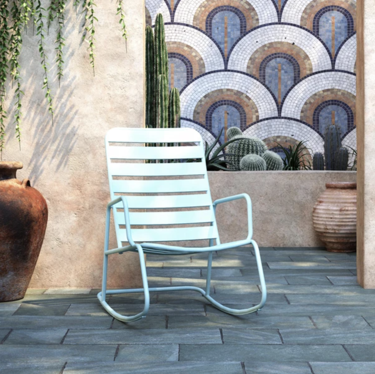 The rocking chair in aqua is outside on a patio