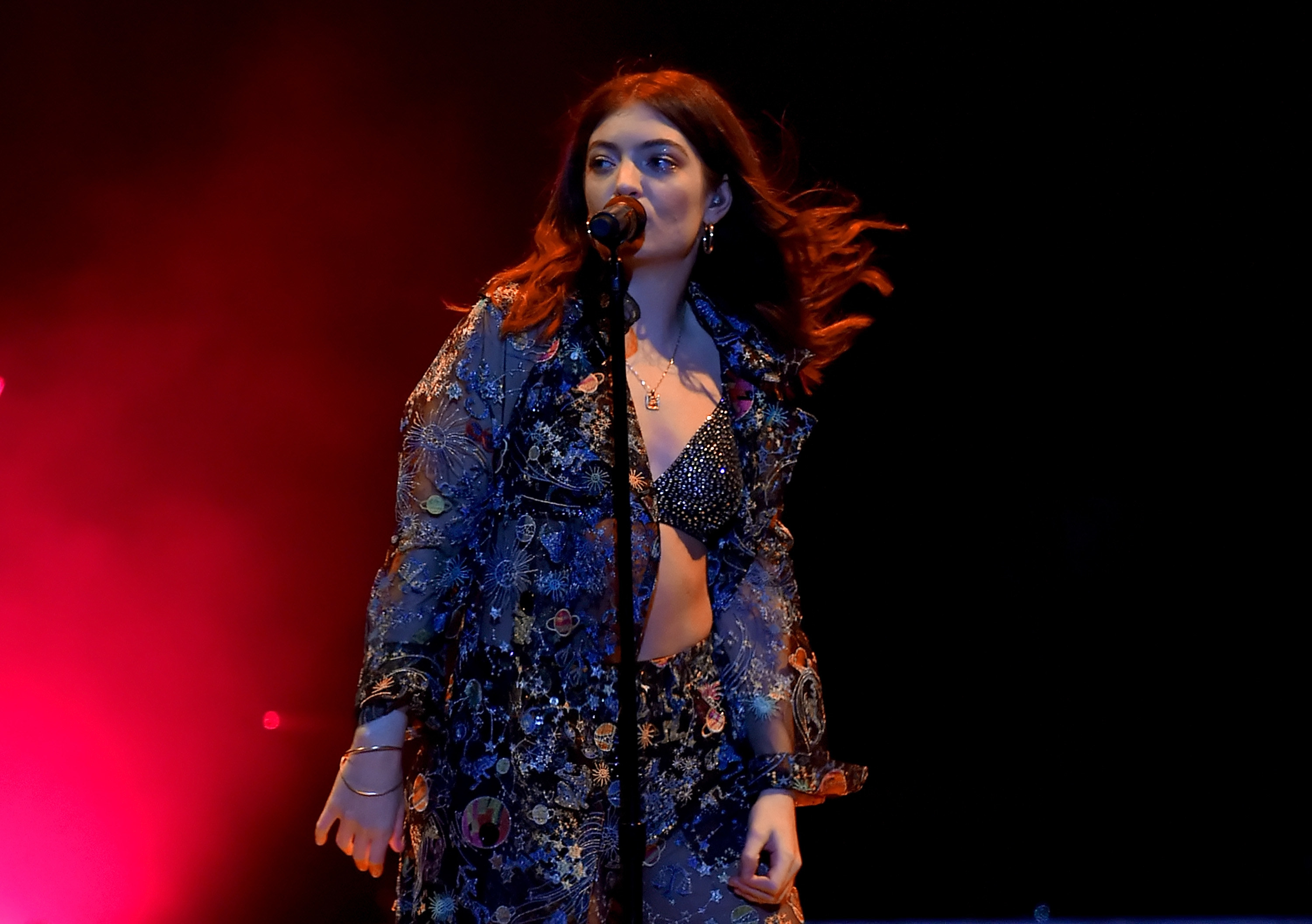 Lorde sings on stage in a matching embellished long sleeve top and pants