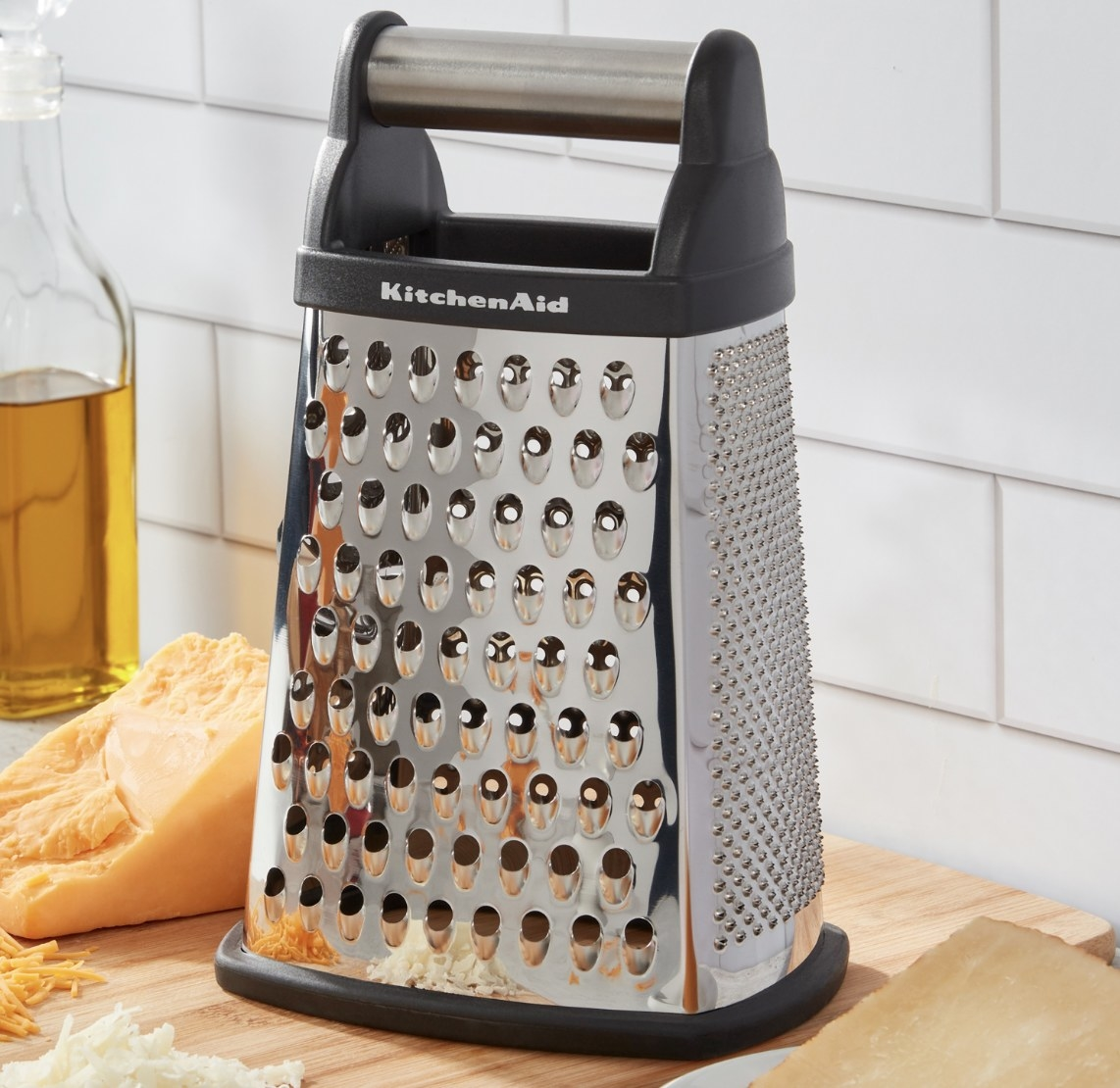 """The stainless steel grater says """"Kitchenaid"""" and has a black handle"""