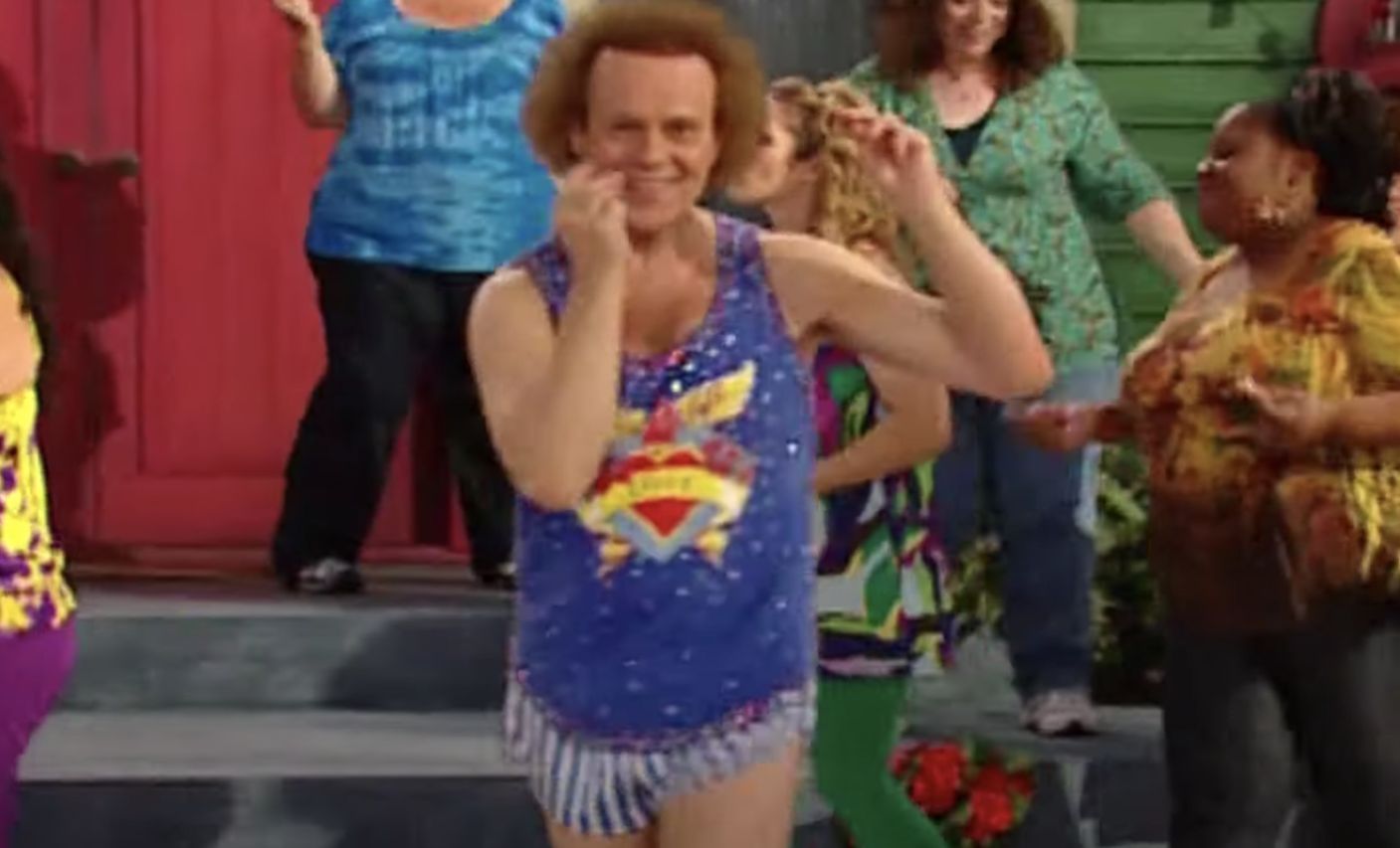 Richard Simmons in a colorful workout outfit, dancing to music