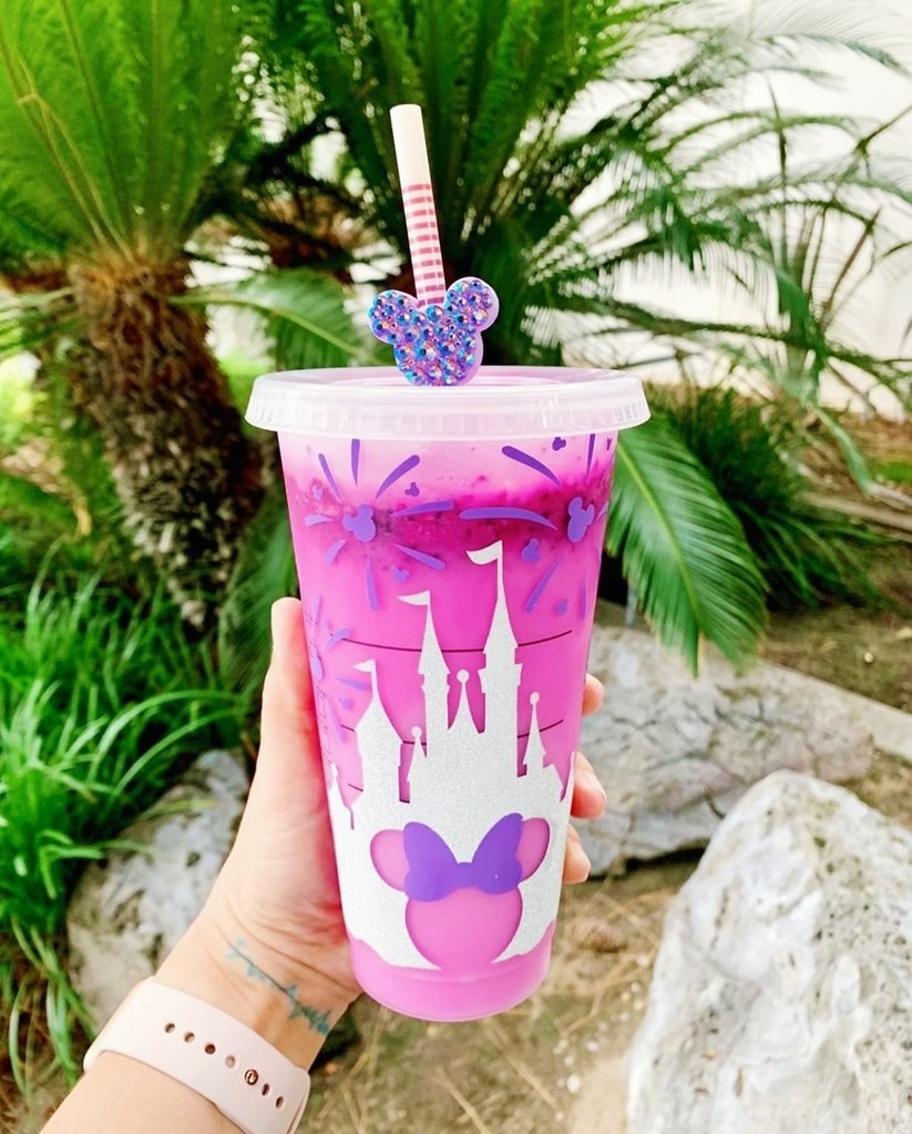 a model holding a purple tumbler with a Minnie Mouse design