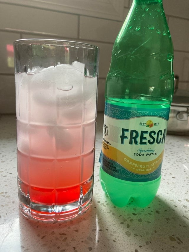 A pink mocktail with a bottle of Fresca to the side.