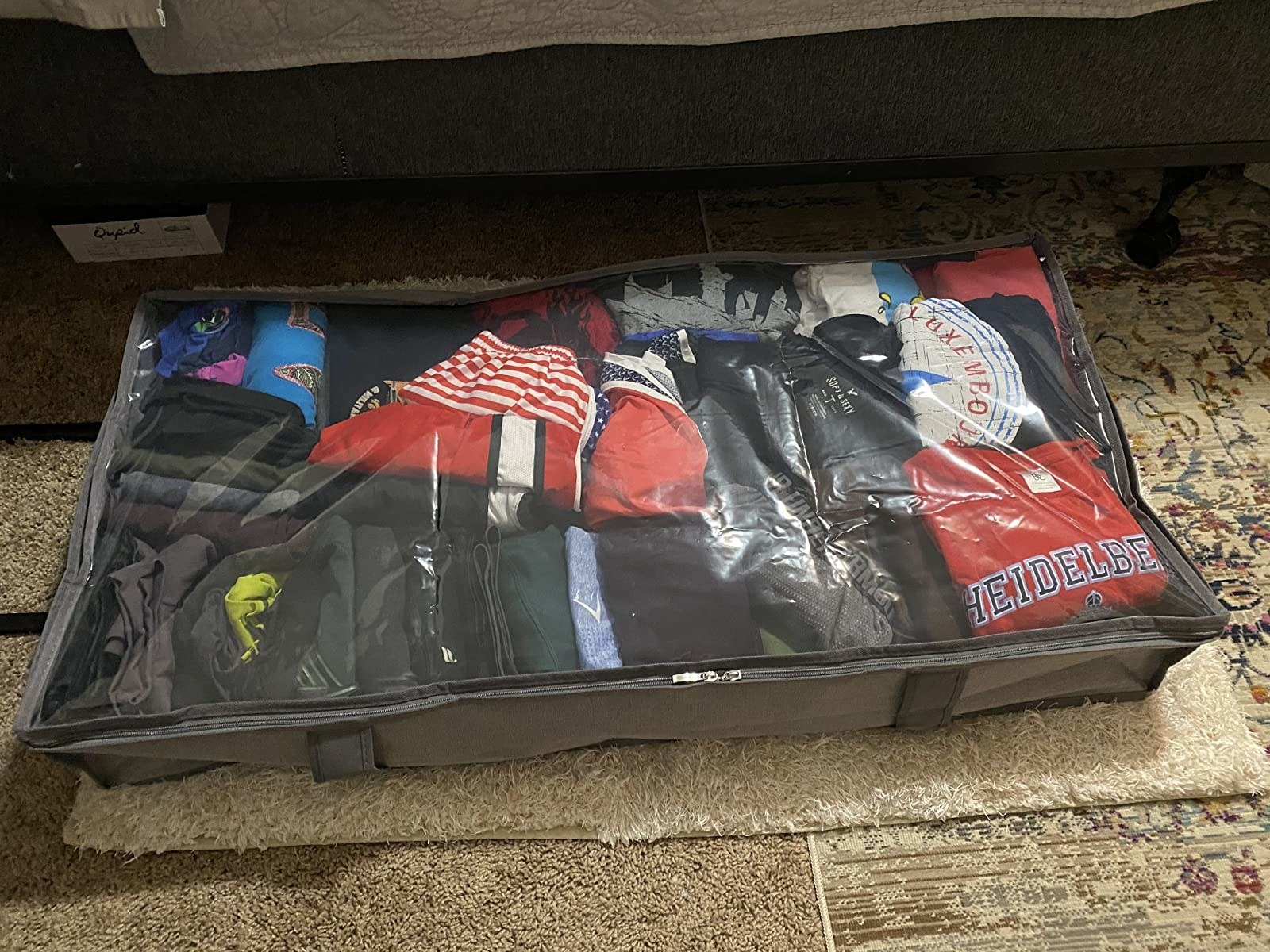 reviewer photo of an underbed storage bin filled with t shirts and leggings