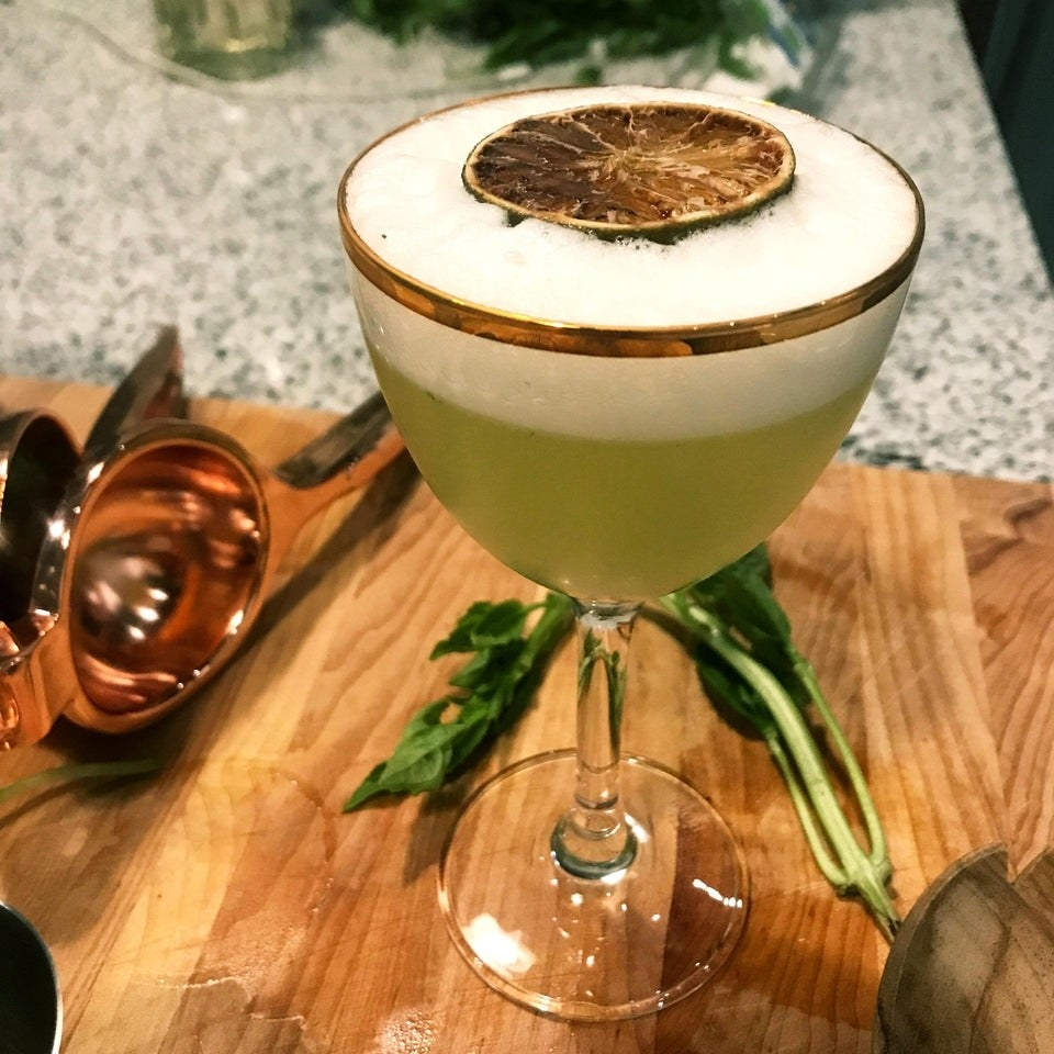 A green mocktail with egg white fizz.