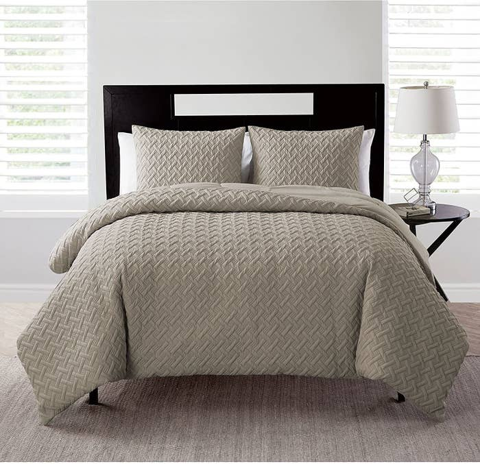 The VCNY Home Nina Collection bedding set on a made bed in taupe