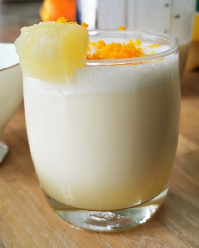A frozen virgin piña colada cocktail topped with orange zest and fresh pineapple