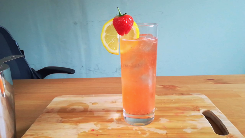 A strawberry lemonade mocktail in a highball glass.
