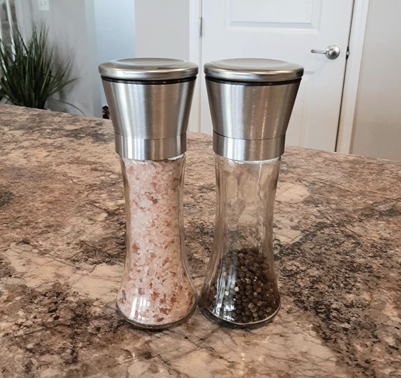 the salt and pepper grinders with pink himalayan salt and black pepper in them