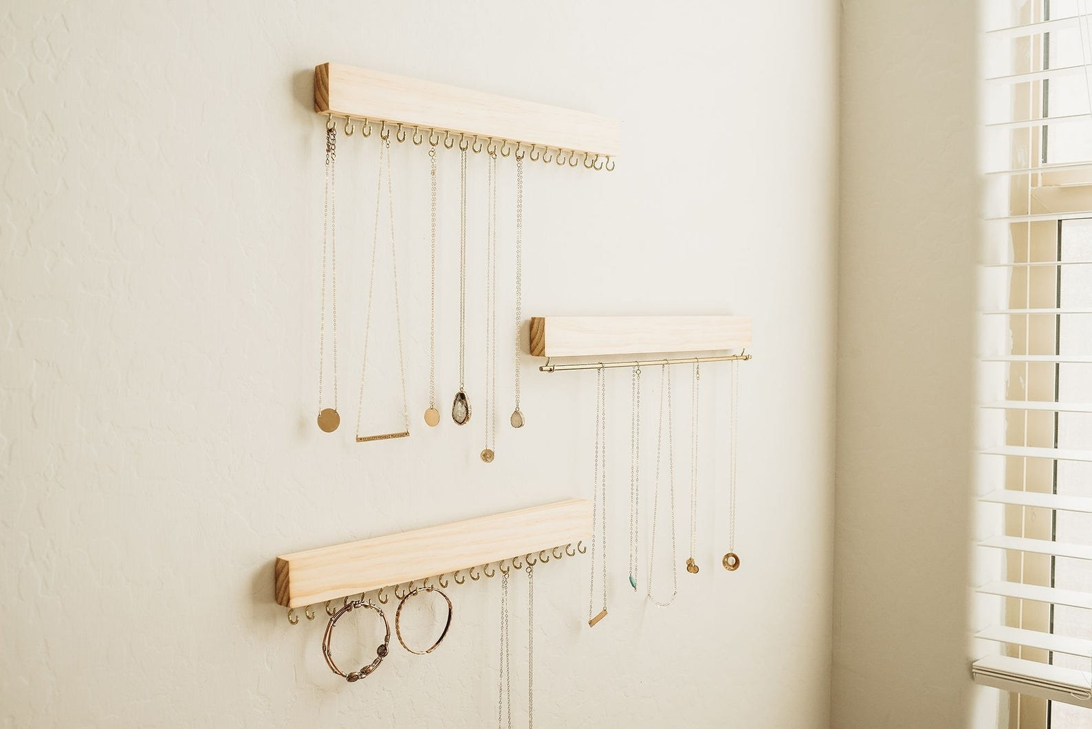 three pieces of wood with hooks on the bottom that are holding jewelry