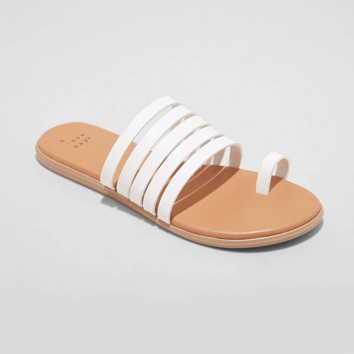 White sandals with five straps and area for one toe, beige sole