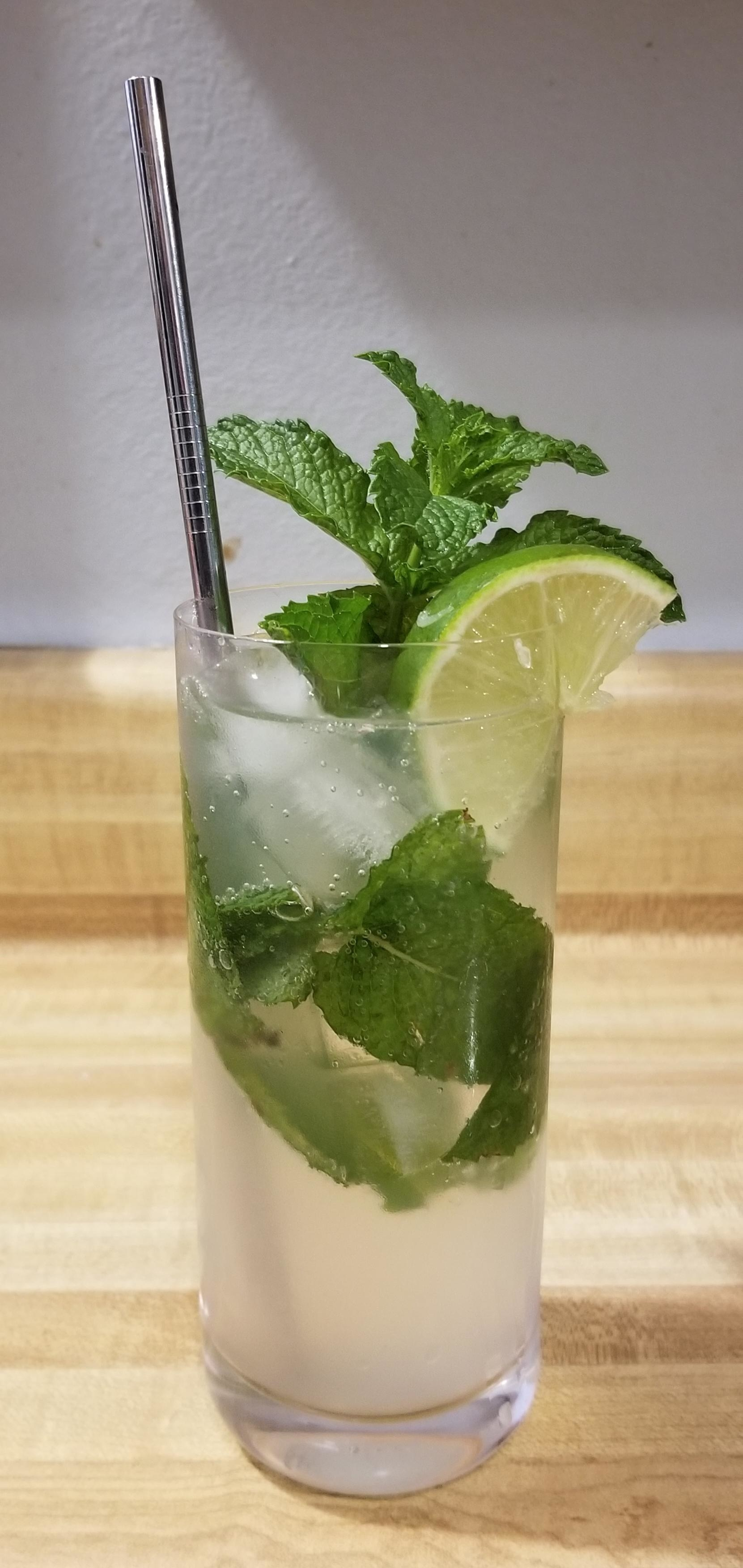 A non-alcoholic mojito garnished with mint and lime.