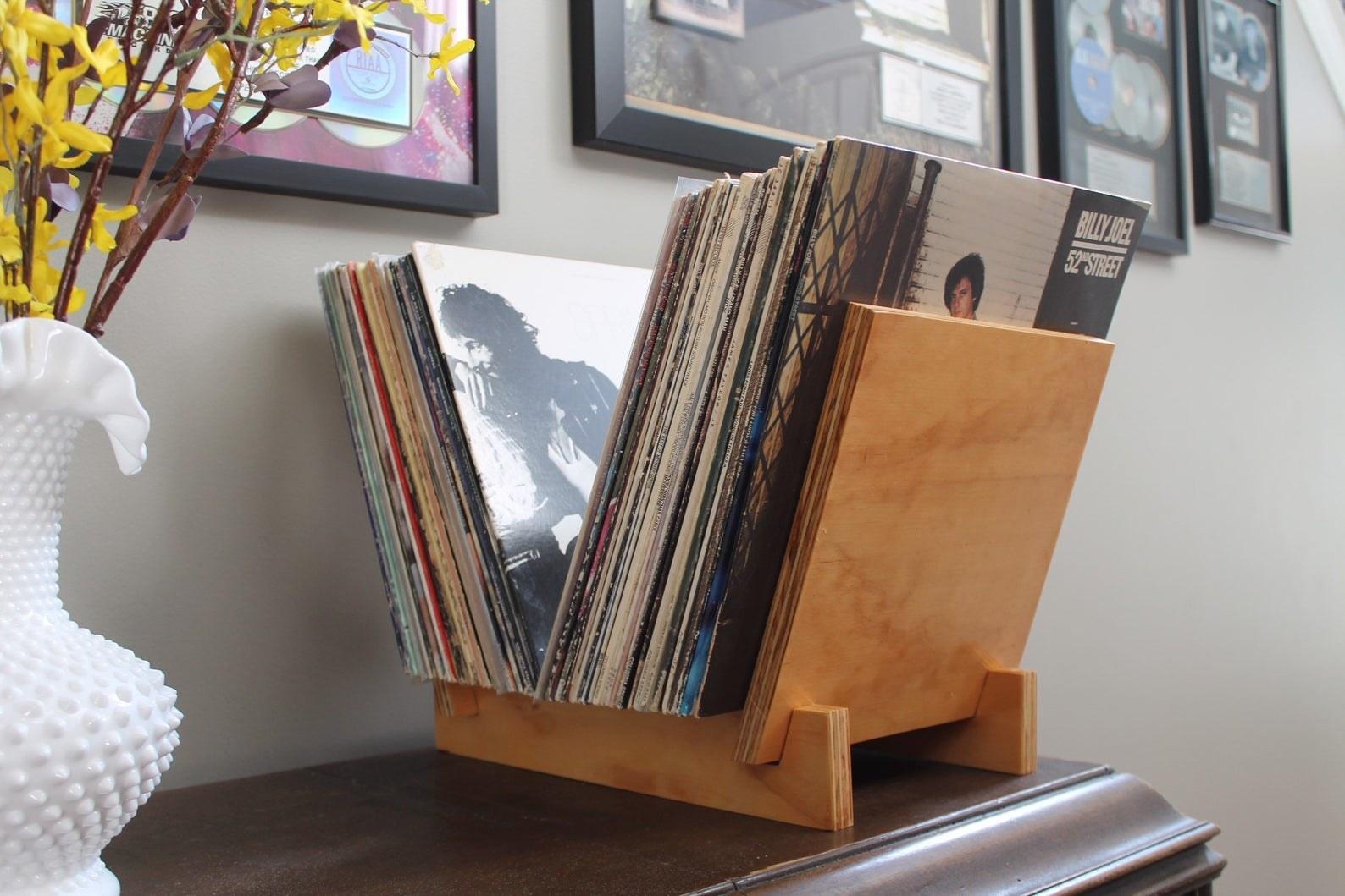 wooden vinyl holder with dozens of vinyls in it