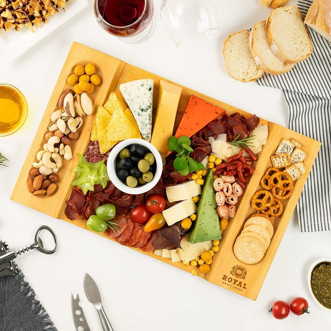 The bamboo cheese board filled with a charcuterie spread